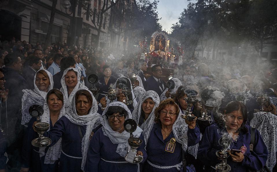 Εκείνη που κάνει θαύματα. Κόσμος μαζεύτηκε για να παρακολουθήσει τις μετανάστριες από το Περού να γιορτάζουν την «Senor de los Milagros» στο κέντρο της Μαδρίτης. Με τα λιβανιστήρια να καίνε και το θυμίαμα να μοσχοβολά στους δρόμους, γιόρτασαν την Πολιούχο της Λίμα με κατάνυξη. (AP Photo/Daniel Ochoa de Olza)