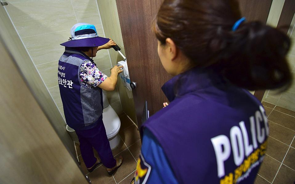 Επιχείρηση τουαλέτα. Πρώτη στην τεχνολογία είναι η Νότιος Κορέα, και στα καλά της και στα κακά της. Ετσι, συχνά-πυκνά η αστυνομία φροντίζει με ειδικό ανιχνευτή να σκανάρει τις γυναικείες τουαλέτες για μικροκάμερες, προφανώς συχνή παράβαση, για την ακόμα ανδροκρατούμενη χώρα.  AFP / JUNG YEON-JE