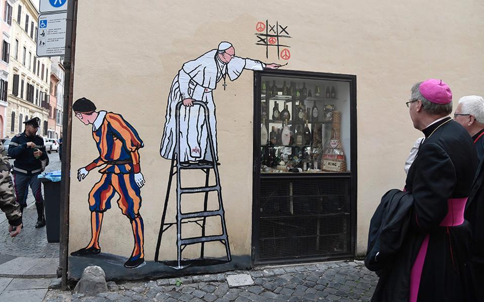 Χαριτωμένος Πάπας. Μια κρυφή στιγμή, μια πονηριά ενός γλυκύτατου Ποντίφικα. Κάπως έτσι σκέφτηκε ο Ιταλός καλλιτέχνης Maupal  και έφτιαξε σε μια γωνιά κοντά στο Βατικανό τον Πάπα να παίζει τρίλιζα με την ειρήνη, ενώ ένας Ελβετός φρουρός αντί να τον προστατεύει, φιλάει τσίλιες.  AFP / TIZIANA FABI