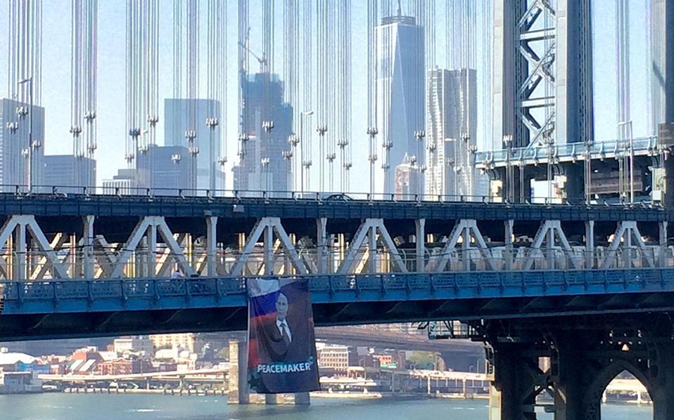 Ο Putin στην Νέα Υόρκη. Ένα τεράστιο πανό με την εικόνα του Ρώσου προέδρου, την σημαία της Συρίας και την λέξη «Ειρηνοποιός», άπλωσαν άγνωστοι στην Manhattan Bridge. Μάρτυρες είπαν ότι δυο άγνωστοι άπλωσαν την τεράστια φωτογραφία περίπου στις 1:45 με την αστυνομία να το κατεβάζει μια ώρα αργότερα χωρίς να προβεί σε συλλήψεις. Nathan Tempey/Gothamist.com via AP)