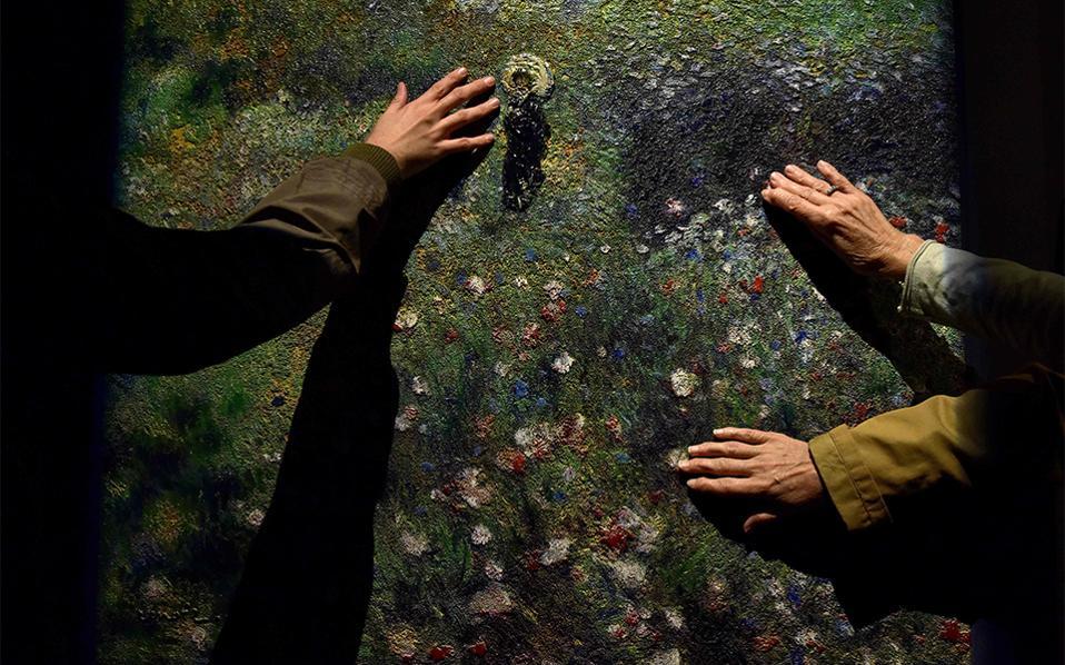Πιάνοντας την ομορφιά. Τυχεροί φιλότεχνοι αγγίζουν τον πίνακα του Pierre-Auguste Renoir «Woman with a Parasol in a Garden». Στην έκθεση «Intimacy» του μουσείου Thyssen-Bornemisza της Μαδρίτης, χρησιμοποιήθηκε μια καινούργια τεχνική που προσθέτει όγκο και υφή στους πίνακες. Η έκθεση θα διαρκέσει μέχρι τις 22 Ιανουαρίου του 2017 AFP / GERARD JULIE