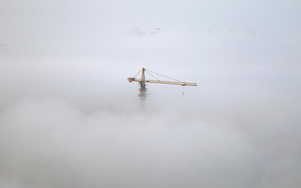 Χτίζοντας σύννεφα. Μπορεί η οικοδομή να είναι μια πεζή διαδικασία, έρχονται όμως στιγμές όπως αυτή, που ο καιρός προσθέτει λίγο μαγεία. Η φωτογραφία είναι από την   Yantai, της επαρχίας Shandong στην Κίνα. China Daily/via REUTERS