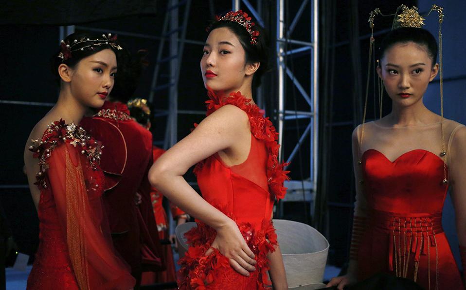 Στα κόκκινα. Πανέτοιμα τα μοντέλα ποζάρουν για τον φακό λίγο πριν ξεκινήσει η επίδειξη μόδας του  σχεδιαστή Tsai Meiyue. Η εβδομάδα μόδας  Mercedes-Benz του Πεκίνου μόλις ξεκίνησε.  EPA/HOW HWEE YOUN