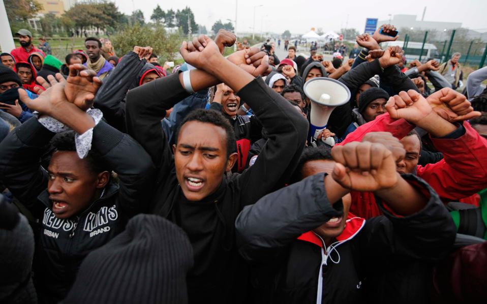 Ομάδα μεταναστών κάνει τη χειρονομία του δεσμώτη μπροστά στις κάμερες για να δείξει την αντιμετώπιση από τις γαλλικές αρχές κατά την κατεδάφιση της «ζούγκλας».