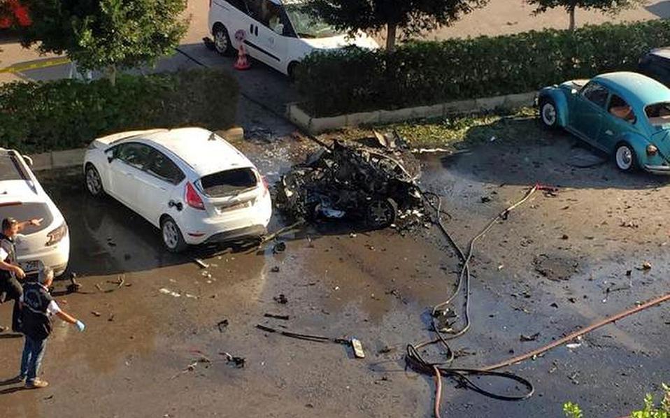 Φωτογραφία από τον χώρο στάθμευσης όπου ένα αυτοκίνητο έχει μετατραπεί σε άμορφη μάζα σιδερικών.