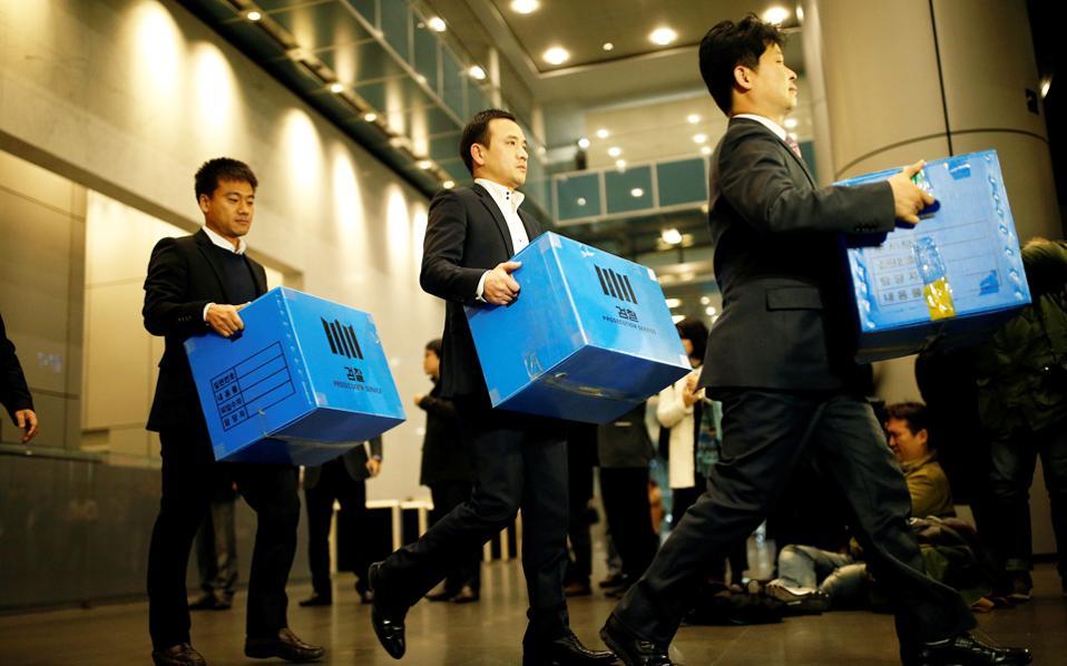 Υπάλληλοι των εισαγγελικών αρχών κουβαλούν κουτιά με έγγραφα του ηλεκτρονικού κολοσσού στο κεντρικό κτίριο της Samsung στη Σεούλ.