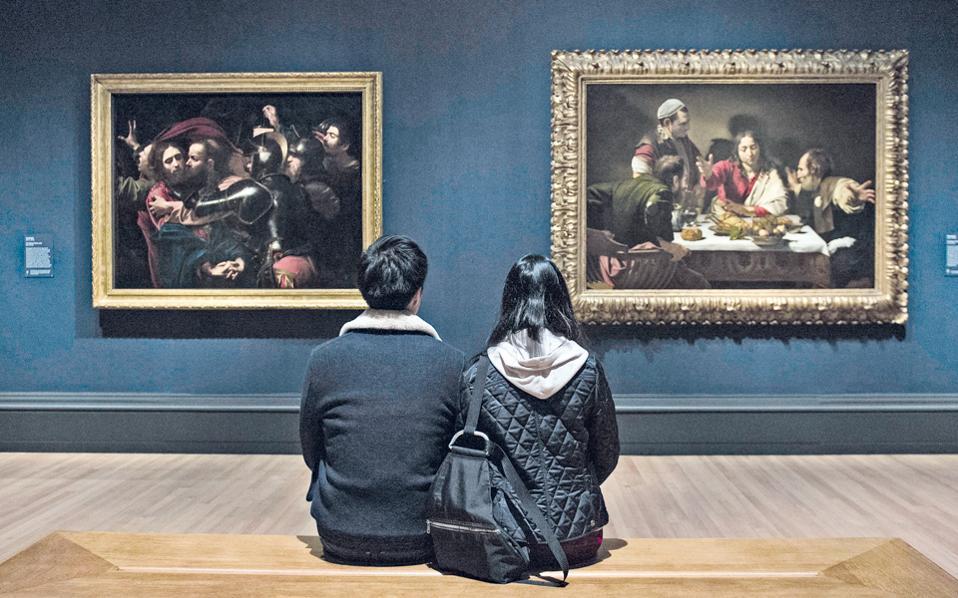 Ο ίδιος ο Καραβάτζο ποζάρει στην άκρη του έργου «Η σύλληψη του Χριστού», όπου ο Ιούδας ετοιμάζεται να δώσει το προδοτικό φιλί στον δάσκαλό του (αριστερά). Το ζευγάρι επισκεπτών στη National Gallery του Λονδίνου, όμως, μοιάζει απορροφημένο από το διπλανό έργο, το «Δείπνο στους Εμμαούς».
