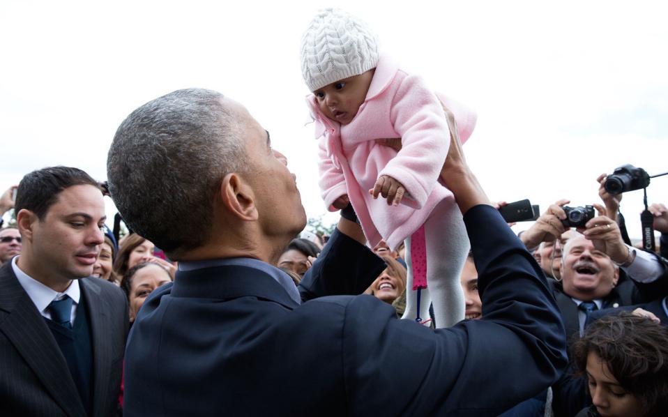 Ο πρόεδρος αγκαλία με ένα κοριτσάκι, σε επίσκεψή του στην Πρεσβεία των ΗΠΑ στην Αθήνα για να τιμήσει το προσωπικό.