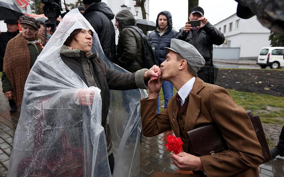Χαρούμενες κυρίες. Αν και τότε οι κύριοι δεν θα αφιέρωναν τόσο χρόνο για να χαιρετήσουν τις κυρίες, χαλάλι. Ο νεαρός, ντυμένος με ρούχα εποχής, δίνει ένα χορταστικό χειροφίλημα στην συναγωνίστριά του, με αφορμή τον εορτασμό της Οκτωβριανής επανάστασης στο Μινσκ. EPA/TATYANA ZENKOVICH