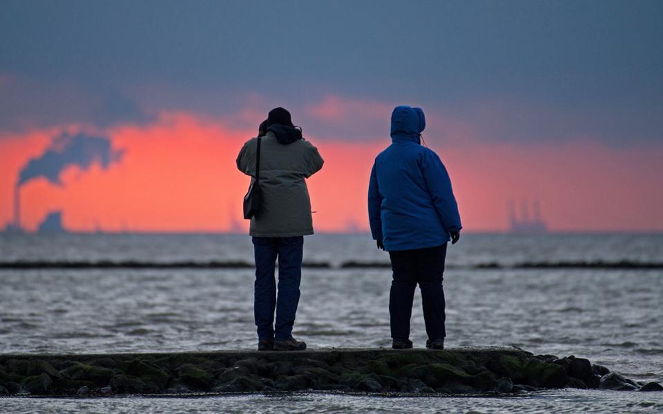 Κάτοικοι περιοχής στη Βόρεια Θάλασσα θαυμάζουν το ηλιοβασίλεμα κοντά στο Ντόρουμ Νόιφλεντ της Γερμανίας.