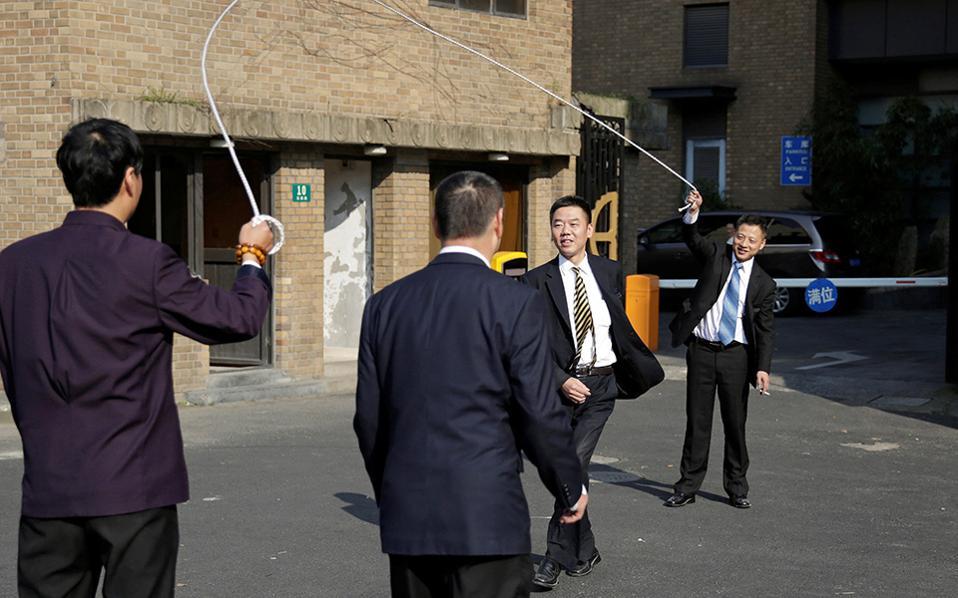 Τα αγόρια διασκεδάζουν. Αν και το παιχνίδι με το σχοινάκι αποτελεί κοριτσίστικο παιχνίδι από πολύ νωρίς, μερικοί άνδρες στην Shanghai έβαλαν στην άκρη τα στερεότυπα και με το τσιγάρο στα χέρια, του έδωσαν και κατάλαβε.  REUTERS/Aly Song