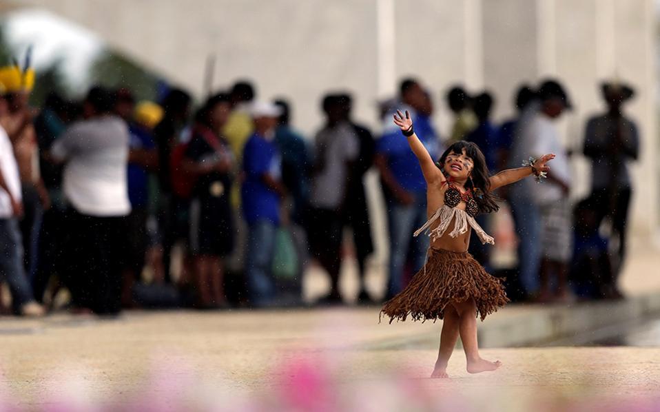 Χορός και αιτήματα. Ντυμένη με τα ρούχα που ορίζει η παράδοση, μια μικρή Ινδιάνα συμμετέχει στην διαμαρτυρία διάφορων φυλών έξω από το κοινοβούλιο στην Brasilia που απαιτούν αναδιανομή γης και επιστροφή των εκτάσεων των προγόνων τους.  REUTERS/Ueslei Marcelino