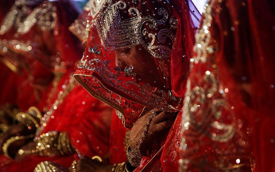Εις γάμου κοινωνία. Με το κεφάλι σκυφτό και ντυμένες με κόκκινο και χρυσό, 21 νύφες περιμένουν να παντρευτούν στον ομαδικό γάμο που διοργανώθηκε για οικονομικά αδύναμους μουσουλμάνους στο  Μumbai.  EPA/DIVYAKANT SOLANKI