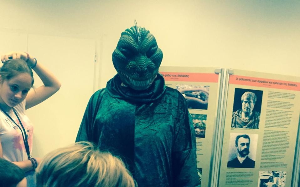 Mε στολή αλιγάτορα, εκπαιδευτής μιλάει στο παιδικό ακροατήριο.