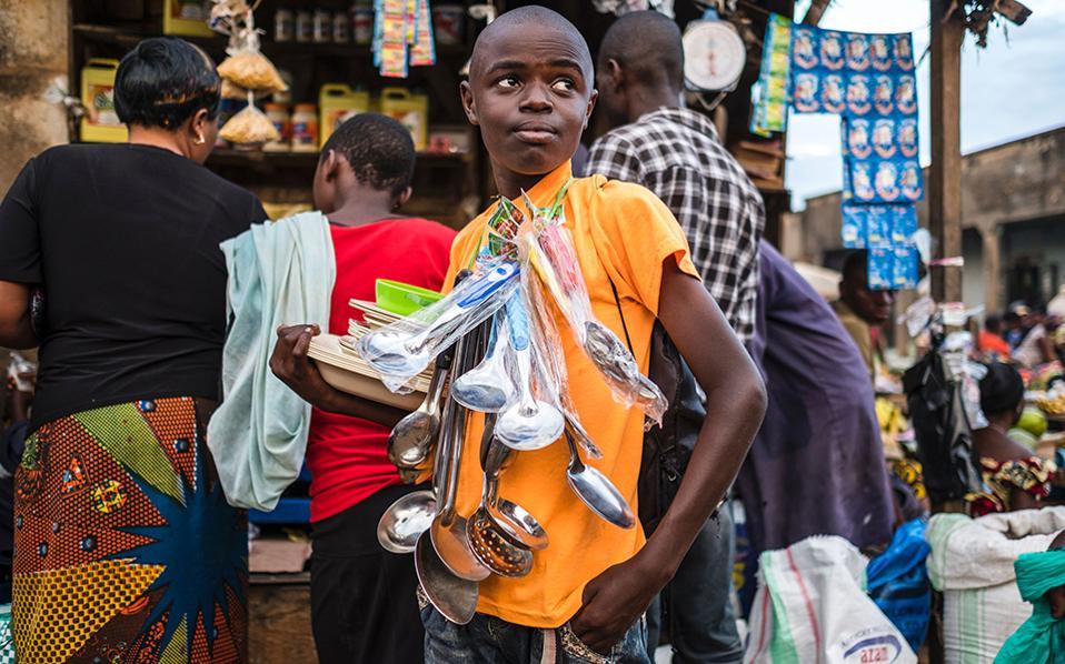 Εθνικ κοσμήματα. Στην αγορά του Beni στο Κονγκό, πουλάει την πραμάτεια του ο νεαρός της φωτογραφίας. Κουτάλες κάθε μεγέθους και για κάθε φαγητό και χρήση περασμένα σαν περιδέραιο στο λαιμό του, ενώ τα πλαστικά πιάτα και πιατέλες τακτοποιημένα στο χέρι του. Καλές δουλειές.AFP / Eduardo Soter