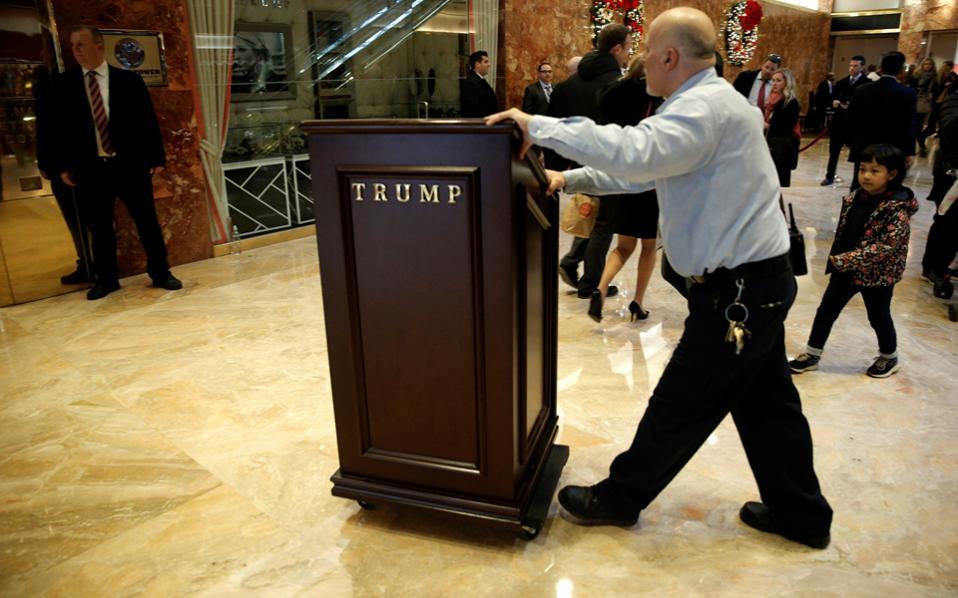 Υπάλληλος μετακινεί αναλόγιο στην είσοδο του Πύργου Τραμπ στη Νέα Υόρκη.