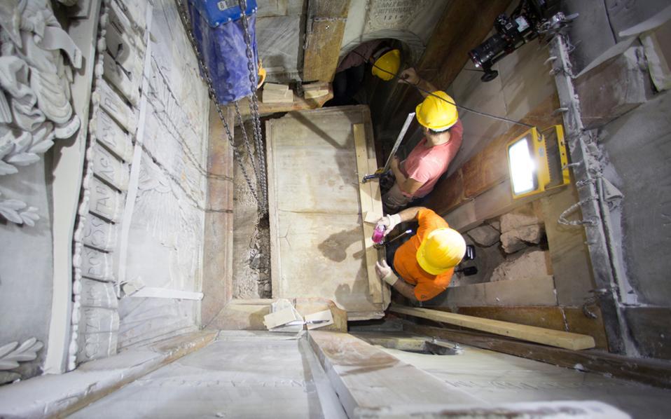 Η στιγμή που τεχνίτες και συντηρητές τραβούν τη μαρμάρινη πλάκα που είχε τοποθετηθεί στον Πανάγιο Τάφο από τον αρχιτέκτονα Κάλφα Κομνηνό.