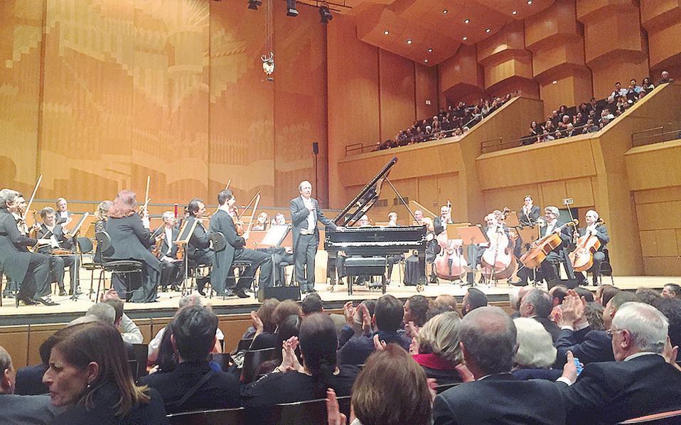 Με το χέρι στην καρδιά, συγκινημένος και ευτυχής για τη θερμή υποδοχή της κατάμεστης Αίθουσας του Μεγάρου, ο πιανίστας-μαέστρος Μurray Perahia ευχαριστεί, ενώ οι μουσικοί του τον χειροκροτούν επίσης (φωτογραφία Ελένη Μπίστικα – 4/12/2016).