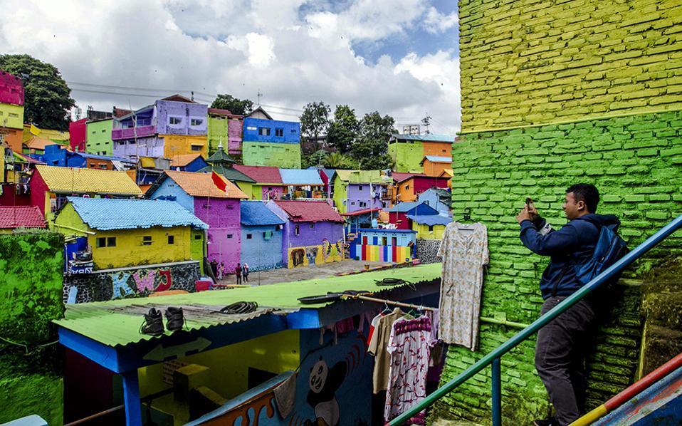 Παράγκες αξιοθέατο. Κόσμος συρρέει για να φωτογραφίσει το πολύχρωμο χωριό Kampung Warna-Warni στην Μalang της Ανατολικής Ιάβας, στην Ινδονησία. Το χωριό που χωρίζει ο ποταμός Brantas έγινε αξιοθέατο της περιοχής σχετικά πρόσφατα, όταν μερικοί έξυπνοι φοιτητές αποφάσισαν να βάψουν σε έντονα χρώματα τα σπιτάκια με σκοπό να τραβήξουν τα φώτα της δημοσιότητας στην παραμελημένη περιοχή και τα κατάφεραν. EPA/FULLY HANDOKO