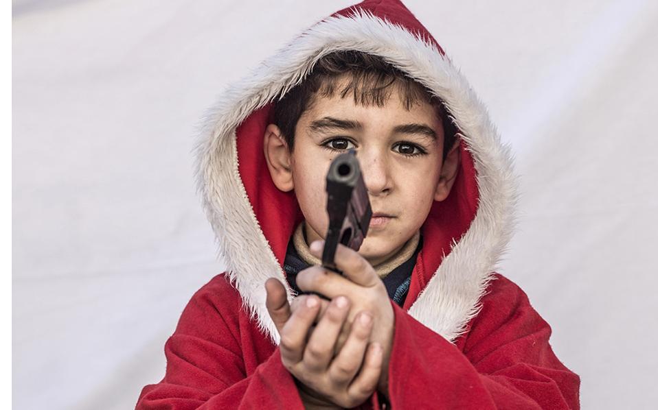 Οι γιορτές των εκτοπισμένων. Με την στολή του Άγιου Βασίλη που γνωρίζει από την χριστιανική του παράδοση, και το όπλο στο χέρι, που τον δίδαξε η βίαιη καθημερινότητά του ο 7χρονος Kayaks ποζάρει για τον φακό. Είναι ένας από τους χιλιάδες χριστιανούς ιρακινούς εκτοπισμένους από τον φόβο του Ισλαμικού Κράτους, που αντιμετωπίζουν με απελπισία το νέο έτος και την πιθανότητα να μην γυρίσουν ούτε το 2017 στα σπίτια τους με ασφάλεια. AP Photo/Manu Brabo