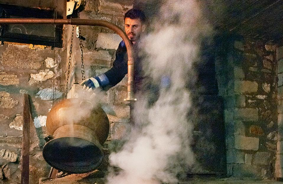 Ο νεαρός Ηλίας βράζει τσίπουρο στο καζάνι της Ζέρβης. (Φωτογραφία: ΚΛΑΙΡΗ ΜΟΥΣΤΑΦΕΛΛΟΥ)
