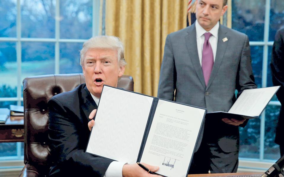 Πρεμιέρα με κινήσεις προστατευτισμού για τον Ντόναλντ Τραμπ στον Λευκό Οίκο. Ο νέος Αμερικανός πρόεδρος υπέγραψε διάταγμα με το οποίο οι ΗΠΑ αποσύρονται από τις διαπραγματεύσεις για τη δημιουργία ζώνης ελευθέρου εμπορίου στον Ειρηνικό Ωκεανό (ΤΡΡ), για την οποία είχε πρωτοστατήσει η κυβέρνηση Ομπάμα. Νωρίτερα, ο Τραμπ είχε καλέσει τον Καναδά και το Μεξικό σε επαναδιαπραγμάτευση της ισχύουσας συμφωνίας ελευθέρου εμπορίου στη Βόρεια Αμερική (NAFTA). Στη φωτογραφία, ο Αμερικανός πρόεδρος επιδεικνύει το διάταγμα που έδωσε τη χαριστική βολή στην ΤΡΡ.