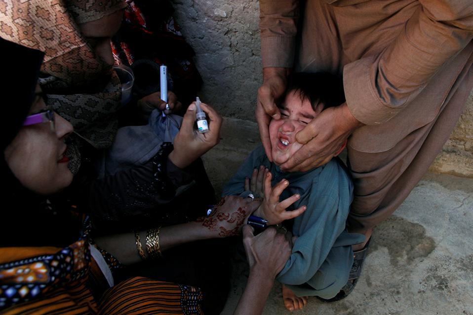 Βασανιστήρια για την υγεία. Με σαγόνι κρατημένο σταθερά, τους αντίχειρες να πιέζουν τα μάγουλα για να ανοίξει το στόμα και τα χέρια δεμένα σφιχτά στο στήθος, ένας πιτσιρικάς εμβολιάζεται από το στόμα για την πολιομυελίτιδα, στους δρόμους της Quetta στο Πακιστάν. REUTERS/Naseer Ahmed