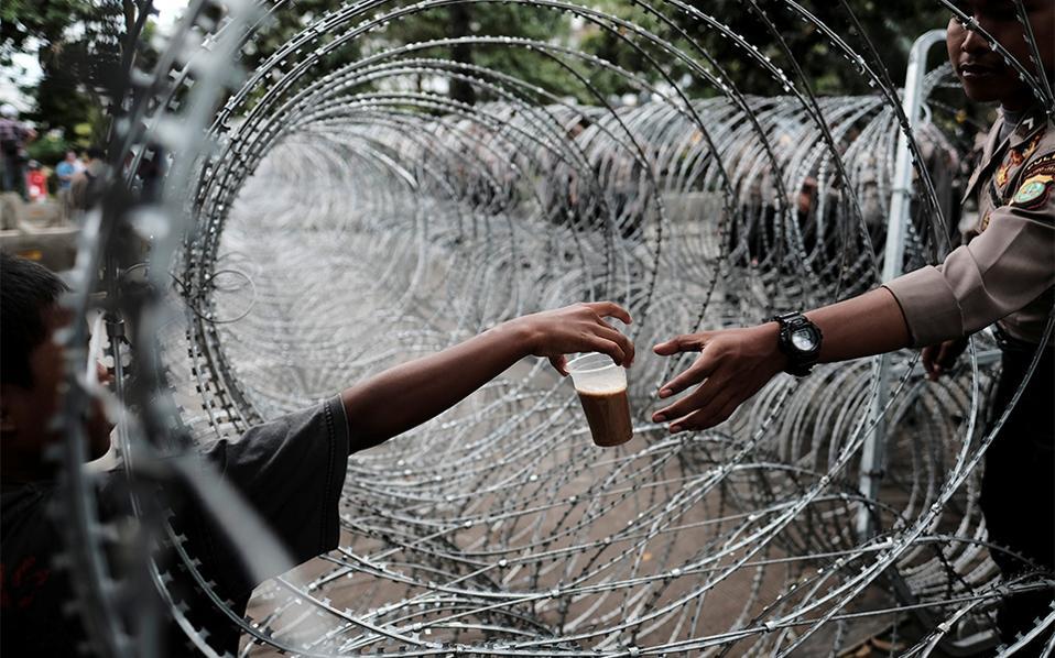 Στα οδοφράγματα. Πολύωρη η παρουσία των αστυνομικών πίσω από τα οδοφράγματα στο δικαστήριο της Jakarata όπου διεξάγεται η δίκη για βλασφημία του χριστιανού κυβερνήτη Basuki Tjahaja Purnama, με την κατηγορία ότι προσέβαλε το Κοράνι.  Ετσι ο καφές από τον πλανόδιο πωλητή είναι απαραίτητος.REUTERS/Beawi