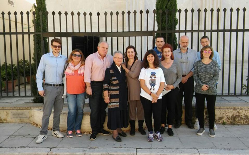 Αναμνηστική φωτογραφία των οικογενειών της διασώστριας και του διασωθέντος έξω από την εβραϊκή συναγωγή της Αθήνας και το μνημείο των «Δικαίων των Εθνών».