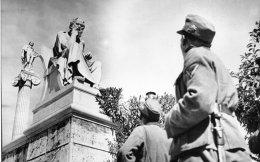 Γερμανοί στρατιώτες κοιτάζουν το άγαλμα του Σωκράτη στην Αθήνα του 1941. Χθες, στην κατάμεστη αίθουσα των Προπυλαίων, ο υπουργός Παιδείας Κώστας Γαβρόγλου, ο αναπληρωτής υπουργός Εξωτερικών της Γερμανίας Μάικλ Ροθ, πανεπιστημιακοί, ερευνητές, φοιτητές, καθηλώθηκαν από τις μαρτυρίες των επιζώντων από την Κατοχή, στην εκδήλωση «Μνήμες από την Κατοχή στην Ελλάδα». Στο πλαίσιο του προγράμματος πραγματοποιούνται συνεντεύξεις στην Ελλάδα με μάρτυρες της περιόδου, μέλη αντιστασιακών οργανώσεων, Εβραίους επιζώντες του Ολοκαυτώματος. Εχουν διεξαχθεί οι 53 από τις 70 προγραμματισμένες συνεντεύξεις.
