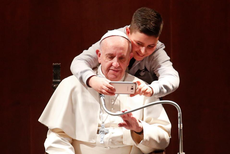 Οικείος. Πρώτα ήταν οι αγκαλιές, τόσες που το Βατικανό έβγαλε ανακοίνωση προς τους πιστούς να είναι πιο προσεκτικοί. Αλλά δεν έφτανε, είναι τόσο οικείος και αγαπητός που δύσκολα κανείς αντιλαμβάνεται τα όρια, όπως ο νεαρός που δεν δίστασε να πλησιάσει τον Πάπα Φραγκίσκο για μια selfie στην εκκλησία St. Mary Josefa της Ρώμης.  REUTERS/Remo Casilli