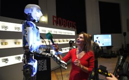 Δημοσιογράφος παίρνει συνέντευξη από έναν εκ των πρωταγωνιστών της έκθεσης «Robots», που εγκαινιάστηκε αυτή την εβδομάδα.