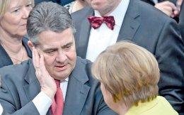 Η καγκελάριος Μέρκελ μιλάει στον υπουργό Εξωτερικών Ζίγκμαρ Γκάμπριελ ενώ μπροστά διακρίνεται ο επικεφαλής των Πρασίνων Τζεμ Εζντεμιρ στη γερμανική Βουλή.