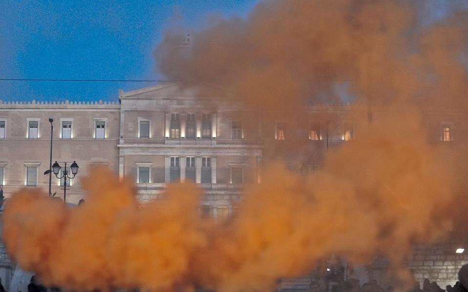 Η μοναδική χρησιμότητα της χθεσινής διαδήλωσης στο Σύνταγμα ήταν αυτή η ασυνήθιστη άποψη της Βουλής, τυλιγμένης στο κόκκινο σύννεφο του καπνογόνου...