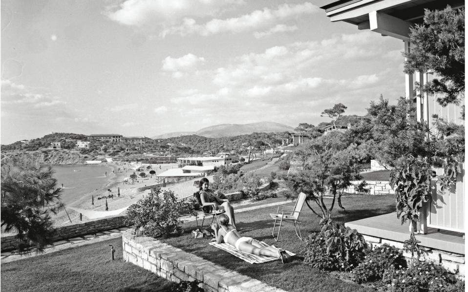 Ενοικοι μιας από τις καμπάνες απολαμβάνουν τον ήλιο στο γκαζόν, με φόντο τη Λαϊκή Πλαζ, το 1961.