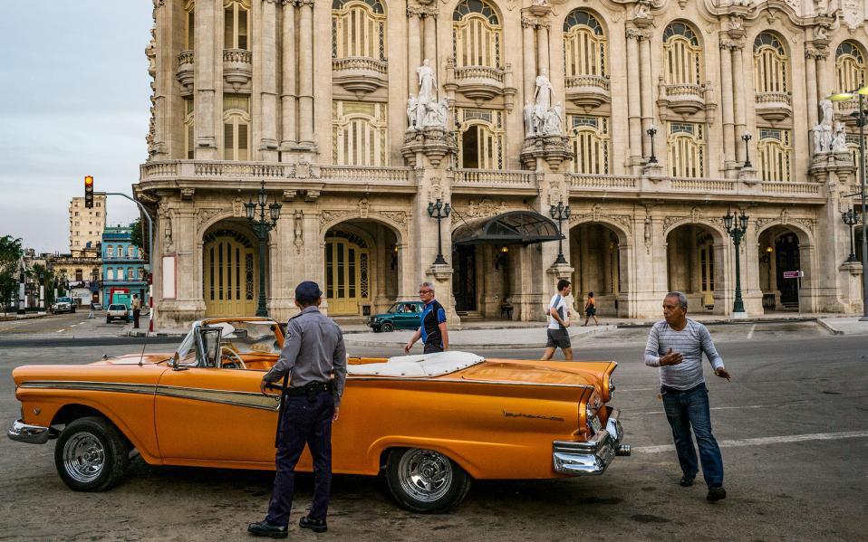 Ενας οδηγός τρέχει να γλιτώσει την κλήση μπροστά από το επιβλητικό Gran Teatro de La Havana - εκεί μίλησε και ο Μπαράκ Ομπάμα στην ιστορική επίσκεψή του στην Κούβα.