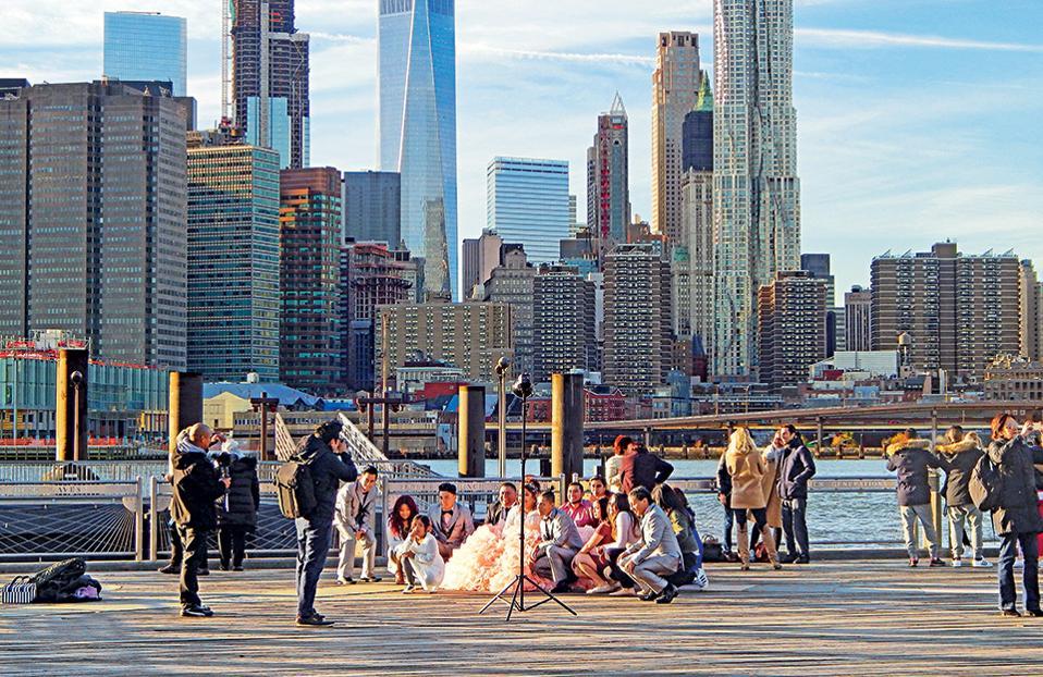 Γαμήλια φωτογραφία, περιμένοντας το East River Ferry. Η νύφη και ο γαμπρός ποζάρουν ανάμεσα σε φίλους με θέα τους ουρανοξύστες του Μανχάταν. (Φωτογραφία: Ιφιγένεια Βιρβιδάκη)