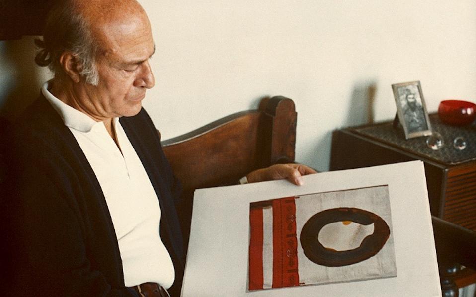 Ο Οδυσσέας Ελύτης στο σπίτι του, το 1980, περιεργάζεται ένα από τα εικαστικά του έργα, για τα οποία επίσης κέρδισε την αγάπη του κοινού. (Αρχείο Ο. Ελύτη / Ι. Ηλιοπούλου)