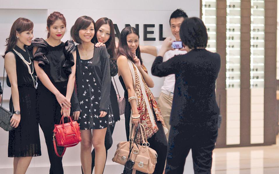 Φωτογραφίες και χαμόγελα έξω από οίκο μόδας στη Σαγκάη. Το χρήμα φέρνει την ευτυχία, γράφει η Βρετανίδα ψυχολόγος και συγγραφέας Κλόντια Χάμοντ στο γερμανικό περιοδικό Spiegel.