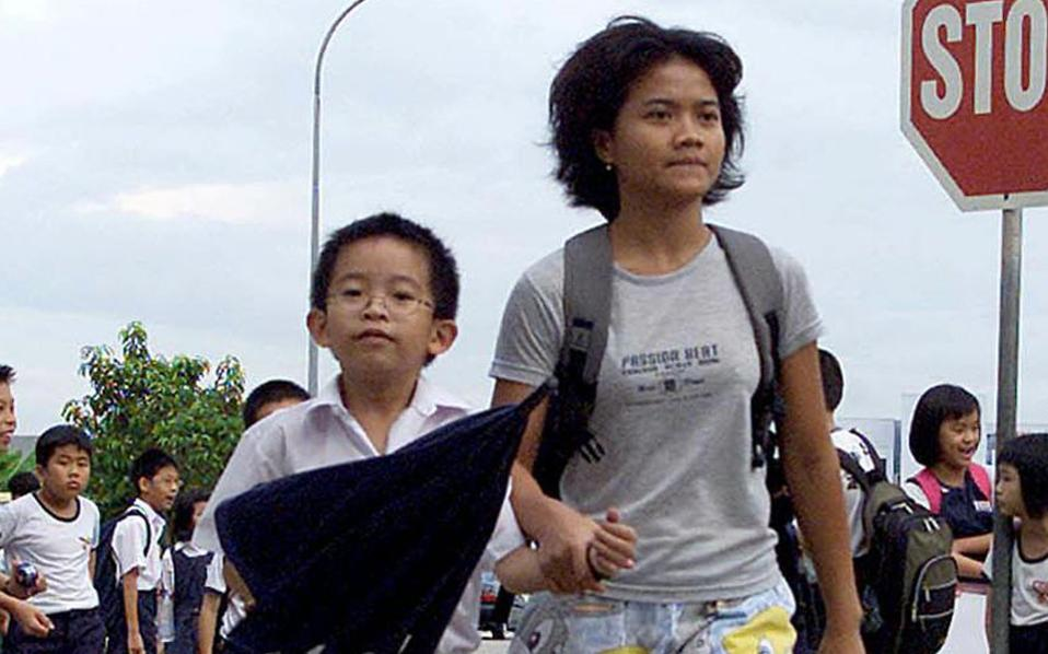 Μαθητής από τη Σιγκαπούρη συνοδεύεται από τη Φιλιππινέζα οικιακή βοηθό της οικογένειάς του.