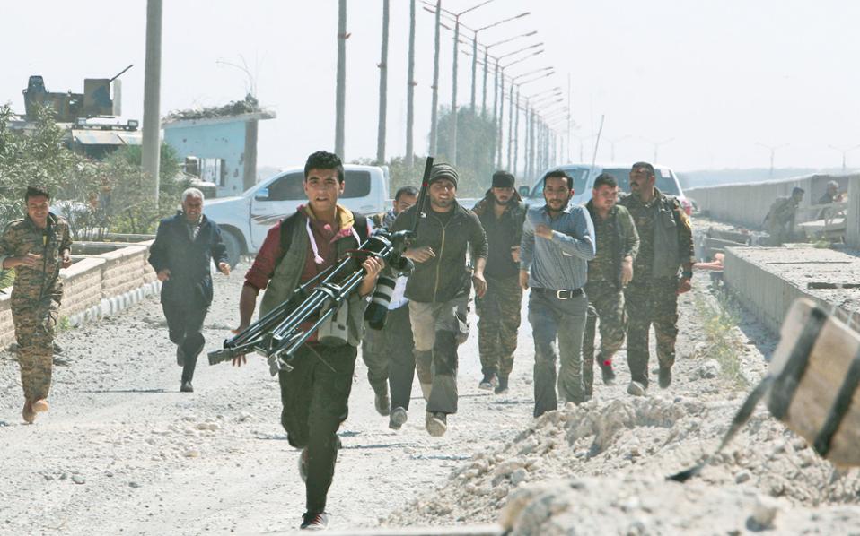 Μηχανικοί, δημοσιογράφοι και Κούρδοι μαχητές μετακινούνται για να προφυλαχθούν, στην Τάμπκα της Συρίας.
