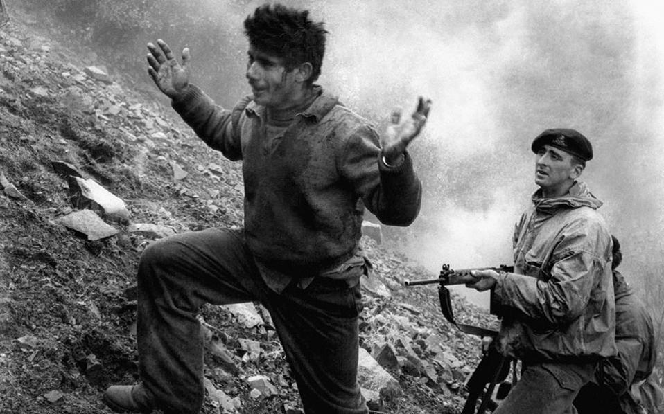 Ο 22χρονος Αυγουστής Ευσταθίου βγαίνει από το κρησφύγετό του υπό την απειλή όπλου Βρετανού στρατιώτη. Ήταν στην ομάδα Αυξεντίου και ήταν μαζί του όταν οι Βρετανοί ανακάλυψαν το κρησφύγετό τους και μετά από πολύωρη μάχη κατέληξαν να πετούν εμπρηστικές βόμβες με αποτέλεσμα τον θάνατο του Γρηγόρη Αυξεντίου το 1957. (AP Photo)