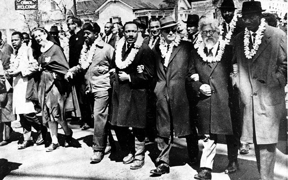 Ο Δρ. Μάρτιν Λούθερ Κινγκ περπατά με άλλους πρωτεργάτες της μάχης υπέρ της πολιτικής ισότητας, καθώς περπατούν προς τη Σέλμα του Μοντγκόμερι το 1965. Στόχος της ιστορικής πορείας ήταν η αναγνώριση του δικαιώματος ψήφου για τους Αφροαμερικάνους. (AP Photo)
