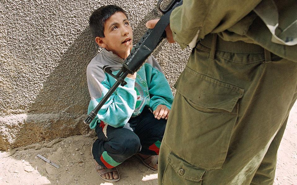 Ένα παιδί από την Παλαιστίνη συλλαμβάνεται από έναν Ισραηλινό στρατιώτη επειδή πετούσε πέτρες στα ισραηλινά στρατεύματα, στη Λωρίδα της Γάζας, το 1994. (AP Photo/Michel Euler)