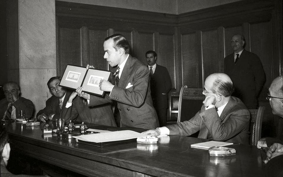 Ο υπουργός Συντονισμού της κυβέρνησης Παπάγου, Σπύρος Μαρκεζίνης, παρουσιάζει μακέτα ομολογιών Αναγκαστικού Δανείου στην αίθουσα εκδηλώσεων του Κεντρικού Καταστήματος.  Η φωτογραφία χρονολογείται τον Μάρτιο του 1954, λίγες μέρες πριν από τη σύγκρουση του Μαρκεζίνη με τον Παπάγο και την αποχώρηση του πρώτου από το κόμμα.