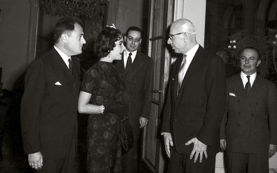 Τον Φεβρουάριο του 1958, ο διοικητής της ΤτΕ Ξενοφώντας Ζολώτας (δεξιά) παραθέτει εκδήλωση στο ξενοδοχείο «Μεγάλη Βρεταννία» προς τιμήν της Αμερικανίδας σταρ Ελίζαμπεθ Τέιλορ, που συνοδεύεται από τον σύζυγό της Μάικλ Τοντ.