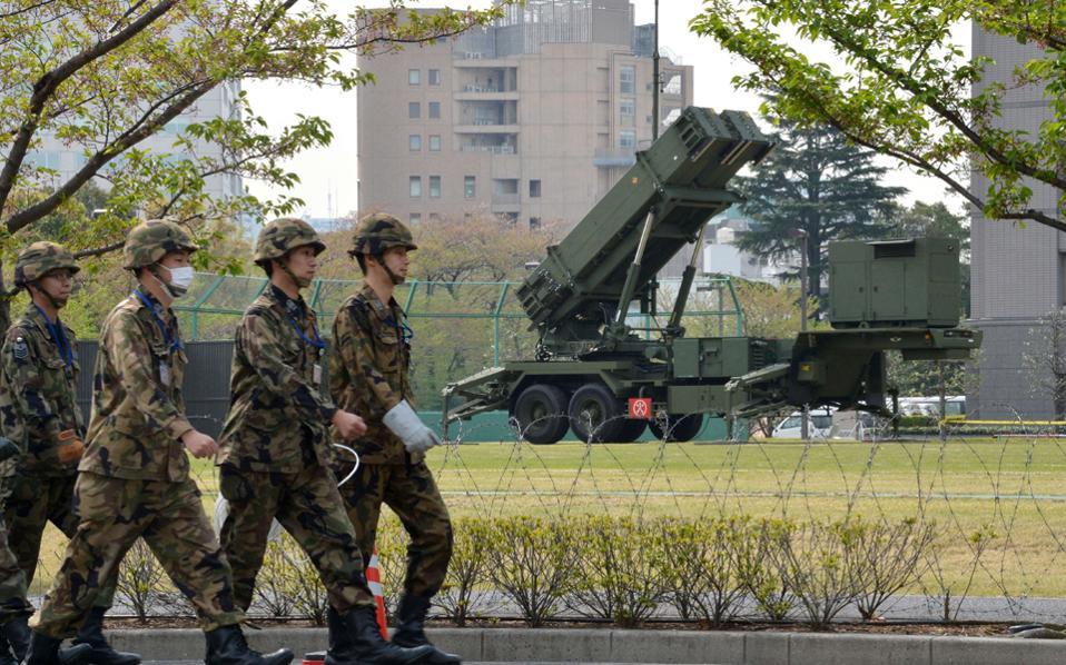 Ιάπωνες στρατιώτες περνούν μπροστά από συστοιχία πυραύλων του αντιαεροπορικού συστήματος Πάτριοτ, που έχει αναπτυχθεί στο προαύλιο του υπουργείου Αμυνας στο Τόκιο.