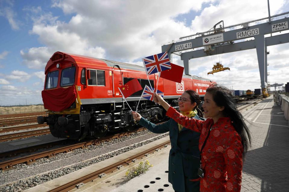 Από την Αγγλία στην Κίνα. Με σημαιάκια των δύο χωρών οι Κινέζες της φωτογραφίας ξεπροβοδίζουν το τρένο από το  Stanford-le-Hope. Το τρένο είναι γεμάτο βρετανικά προϊόντα που θα εξαχθούν στην Κίνα μιας και αυτή είναι η πρώτη απευθείας γραμμή που εγκαινιάζεται γι αυτόν τον σκοπό. Μόνο που στο πλάι το τρένο φέρει το γερμανικό λογότυπο των DB.  REUTERS/Peter Nicholls