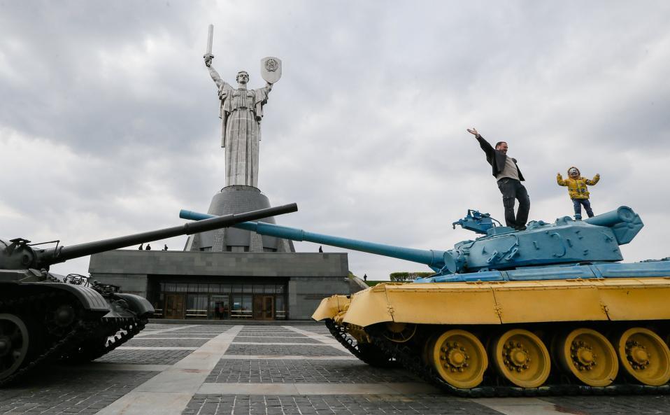 Πόζα. Πάνω στο βαμμένο με τα χρώματα της σημαίας τανκ, πατέρας και γιος ποζάρουν για τον φακό με φόντο το μεγαλειώδες και αριστουργηματικό άγαλμα της μητέρας πατρίδας, στην Ουκρανία.  EPA/SERGEY DOLZHENKO