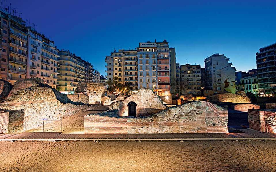 Πλατεία Ναβαρίνου, ανάμεσα στα νεανικά καφέ και τις χαρακτηριστικές μεταπολεμικές πολυκατοικίες που ορίζουν το σύγχρονο αστικό προφίλ της Θεσσαλονίκης, οι μισογκρεμισμένοι τοίχοι του ρωμαϊκού ανακτόρου συνεχίζουν την πορεία τους στους αιώνες – πρόκειται για τμήμα του Γαλεριανού συγκροτήματος, χειροπιαστή απόδειξη της ακμής που έζησε η πόλη προς τα τέλη του 3ου αιώνα. Τα σημάδια της ιστορίας και τα ίχνη των πολιτισμών, διάσπαρτα στην πόλη, διαμορφώνουν τη φυσιογνωμία της και της χαρίζουν μια επιπλέον γοητεία. Ισως κι ένα μυστήριο. Οπως συμβαίνει και με τον ουρανό στη φωτογραφία, του οποίου αυτό το ακαθόριστο μπλε χρώμα σε αφήνει να απορείς· αυτό που αναρωτιόταν κι ο Ελύτης: «Ξημερώματα είναι ή σκοτεινιάζει;». Κάτι αρχίζει ή κάτι τελειώνει; Τα φώτα στα διαμερίσματα στο βάθος μόλις άναψαν ή είναι αυτά που δεν έκλεισαν όλη τη νύχτα; © Αλέξανδρος Αβραμίδης